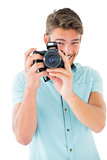 Handsome young man holding digital camera