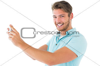 Handsome young man taking photo with smartphone