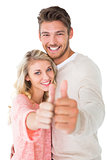Attractive couple showing thumbs up to camera