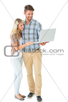Attractive couple standing and using laptop
