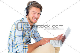 Handsome young man sitting using laptop