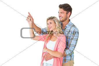 Attractive young couple embracing and pointing