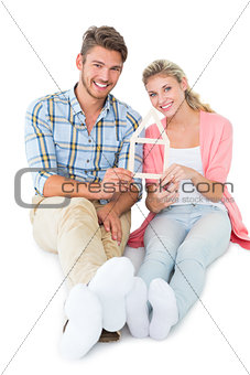Attractive young couple sitting holding a house outline