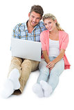 Attractive young couple sitting using laptop