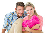 Attractive young couple sitting holding heart cushion