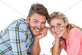 Attractive young couple lying and smiling at camera