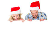 Festive couple smiling from behind poster