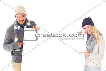 Attractive couple in winter fashion showing poster