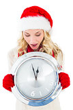 Festive blonde holding large clock