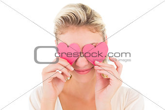 Attractive young blonde holding hearts over eyes