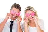 Attractive young couple holding pink hearts over eyes