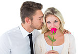 Handsome man kissing girlfriend on cheek holding a rose