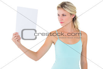 Angry blonde holding a sheet of paper