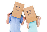 Couple wearing sad face boxes on their heads