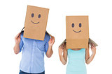 Couple wearing emoticon face boxes on their heads
