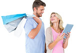 Attractive young couple holding shopping bags looking at tablet pc