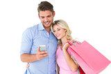 Attractive young couple holding shopping bags looking at smartphone