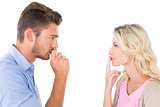 Young couple staying silent with fingers on lips