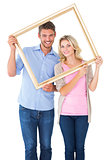 Attractive young couple holding picture frame