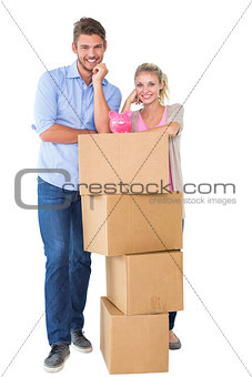Attractive young couple leaning on boxes with piggy bank