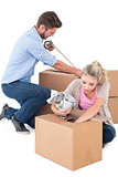 Young couple packing moving boxes