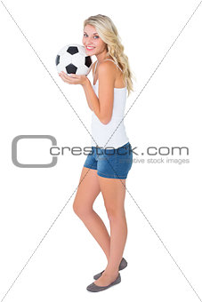 Pretty blonde football fan holding ball