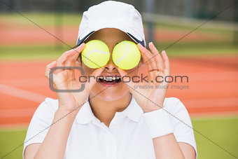 Pretty tennis player holding balls over her eyes