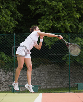 Pretty tennis player jumping and hitting