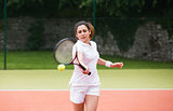 Young tennis player hitting ball