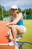 Pretty tennis player smiling on court