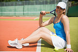 Pretty tennis player sitting on court smiling at camera