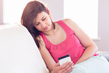 Pretty brunette relaxing on the couch using smartphone