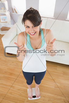 Fit brunette smiling at camera on the weighing scales