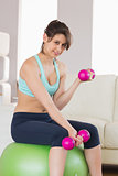 Fit brunette sitting on exercise ball lifting hand weights
