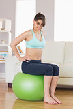 Fit brunette sitting on exercise ball smiling at camera