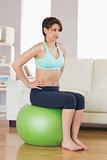 Fit brunette sitting on exercise ball
