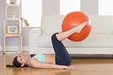 Fit brunette lifting exercise ball with legs