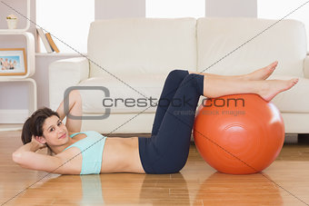Fit brunette doing sit ups with exercise ball