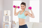 Fit brunette holding dumbbells smiling at camera