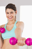 Fit brunette holding pink dumbbells