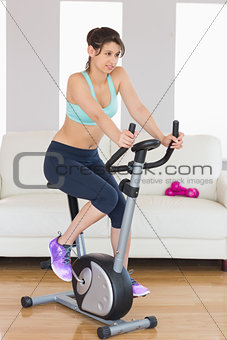 Fit brunette working out on exercise bike