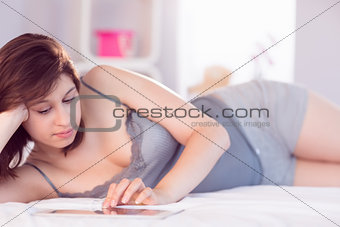Beautiful brunette lying on bed using her tablet pc