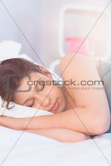 Beautiful brunette lying on bed sleeping