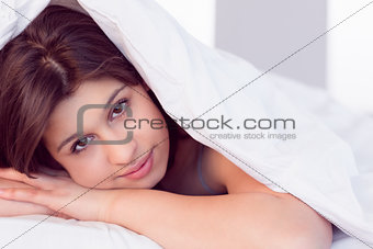 Beautiful brunette smiling at camera under duvet