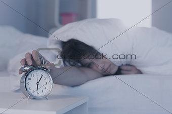 Beautiful brunette hitting alarm clock from under duvet