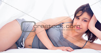 Beautiful brunette smiling at camera under duvet