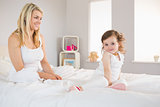 Mother and daughter sitting on bed at home