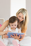 Mother and daughter using digital tablet on bed at home