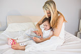 Mother and daughter using digital tablet on bed