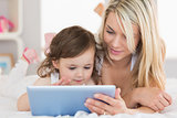 Mother and young daughter digital tablet on bed